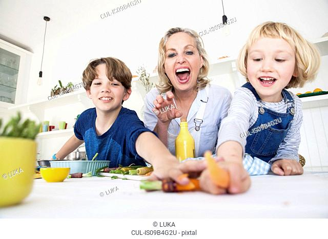Girl and brother reaching for vegetable while preparing food at kitchen table with mother