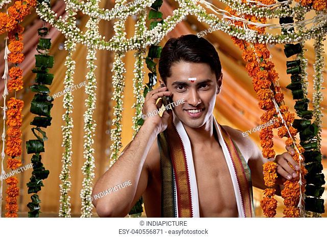 Portrait of groom talking on mobile phone