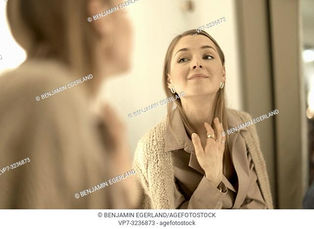 fashionable woman looking at herself in the mirror, in Munich, Germany