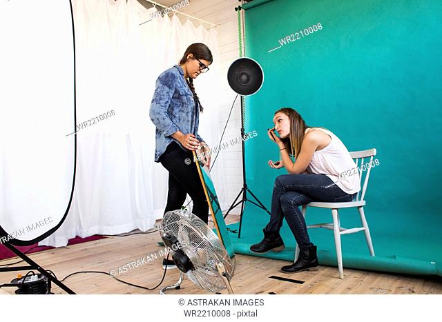 Photo assistant holding mirror for fashion model applying make-up in studio