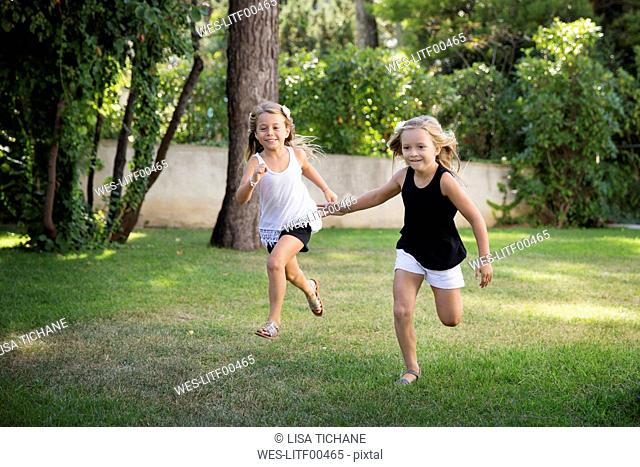 Two little sisters running and racing in the garden