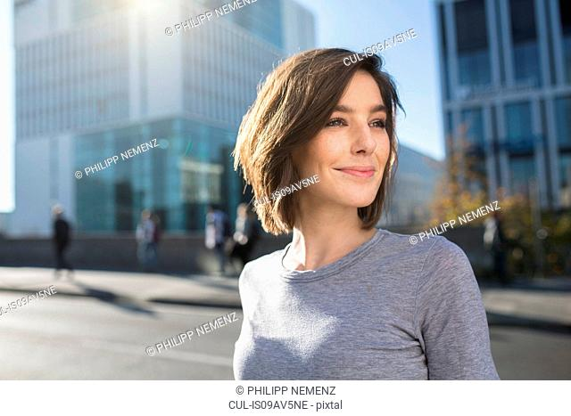 Mid adult woman looking over her shoulder on city road