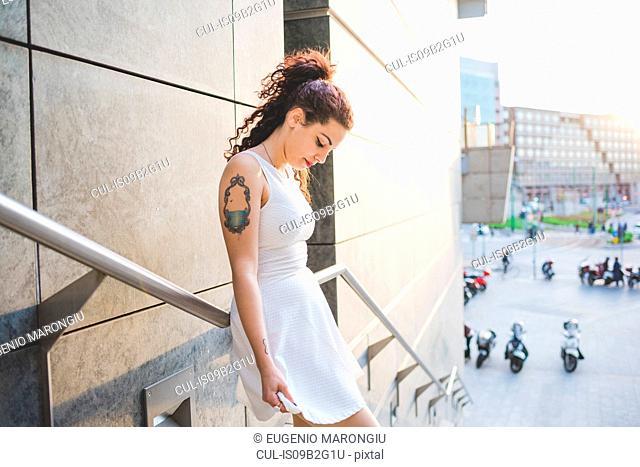 Woman on stairway looking down, Milan, Italy