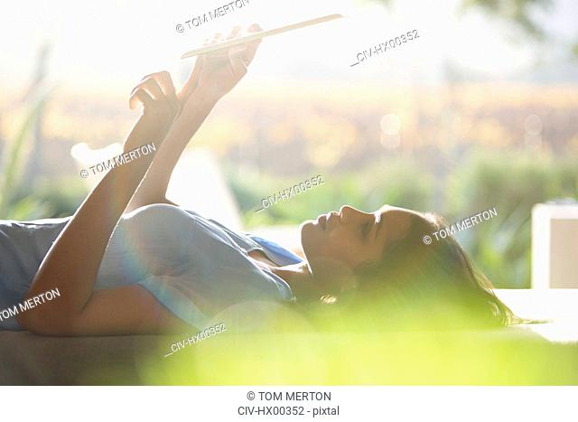 Woman laying and using digital tablet on patio