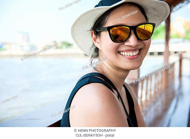 Woman smiling into the camera on a boat on the Chao Phraya river in Bangkok, Thailand