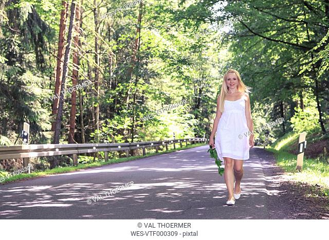 Portrait of a young woman wearing white dress walking on country road
