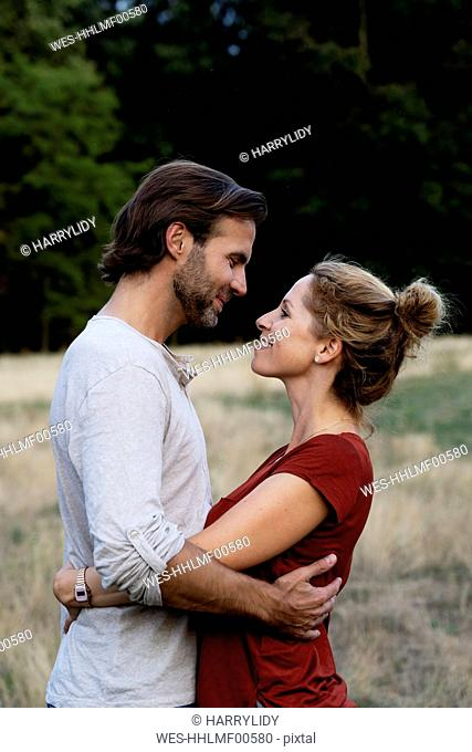 Happy couple in nature, standing face to face, caressing each other