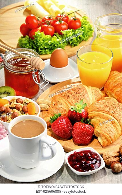 Breakfast consisting of croissants, coffee, fruits, orange juice, coffee and jam. Balanced diet