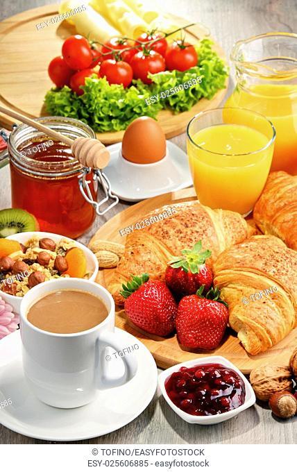 Breakfast consisting of croissants, coffee, fruits, orange juice, coffee and jam. Balanced diet