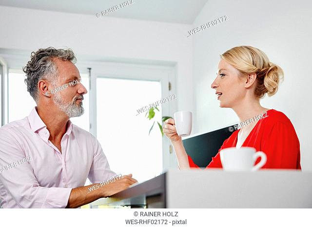 Two colleagues with coffee cups talking in office