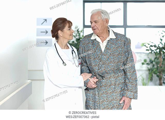 Doctor with elderly patient on hospital floor