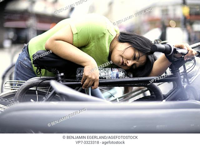 exhausted woman laying on bicycle in city, in Paris, France