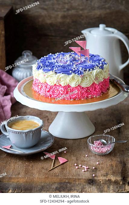 A tri-coloured buttercream cake on a cake stand