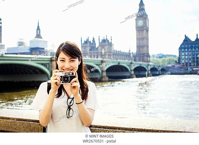 Young Japanese woman enjoying a day out in London, standing on the Queen's Walk by the River Thames