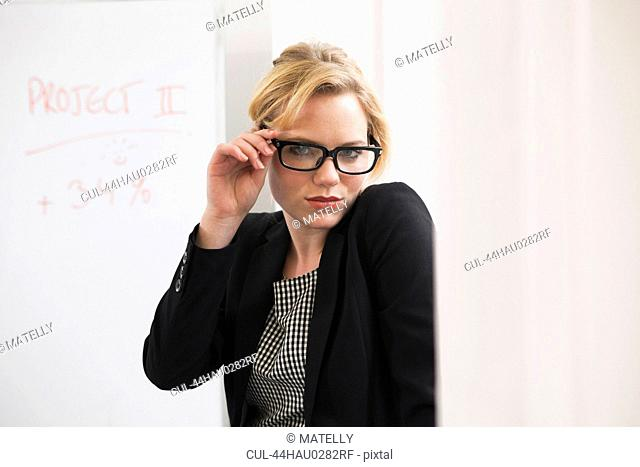 Businesswoman holding glasses in office