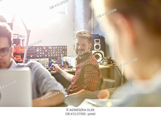 Portrait smiling engineer assembling electronics, using soldering iron in workshop