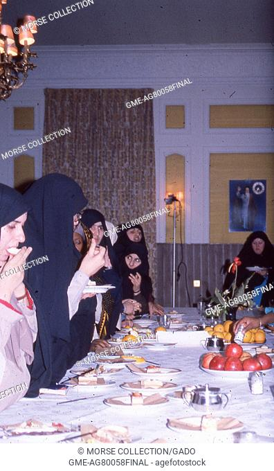 Scene of a group of Muslim women of various ethnicities wearing chadors, eating cake and fruit from a long banquet table at a hotel in Iran, March, 1983