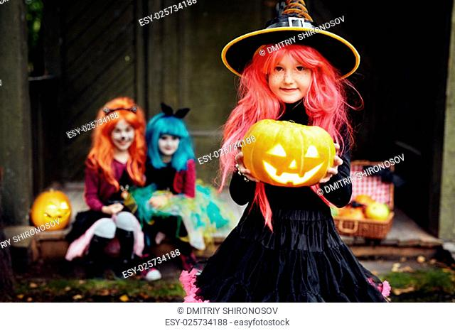 Little Halloween witch holding jack-o-lantern on background of two girls
