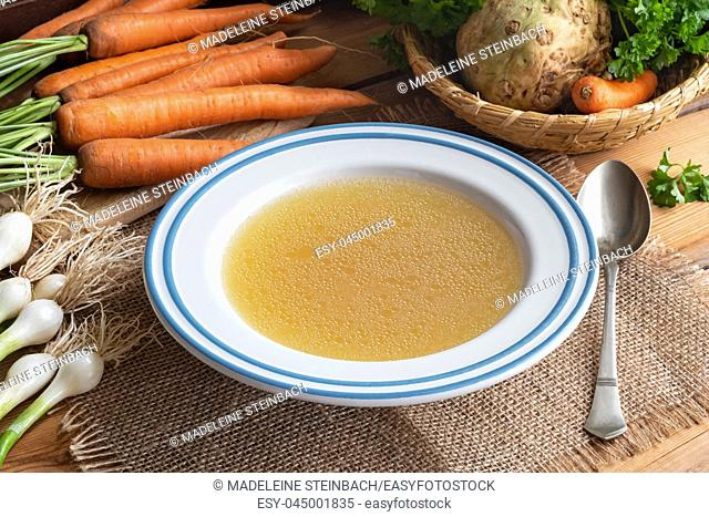 Chicken bone broth with vegetables on a table