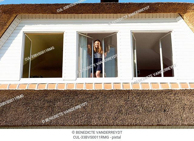 Girl standing in window of home