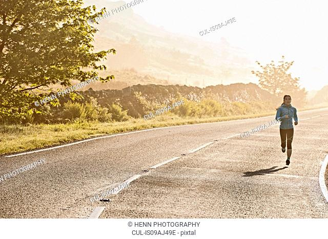 Rear view of female runner running on misty road in morning, Capel Curig, Snowdonia, North Wales, UK