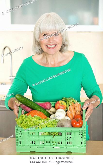 Elderly woman with an organic vegetable box