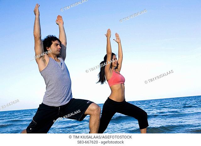 Young couple doing yoga on the beach
