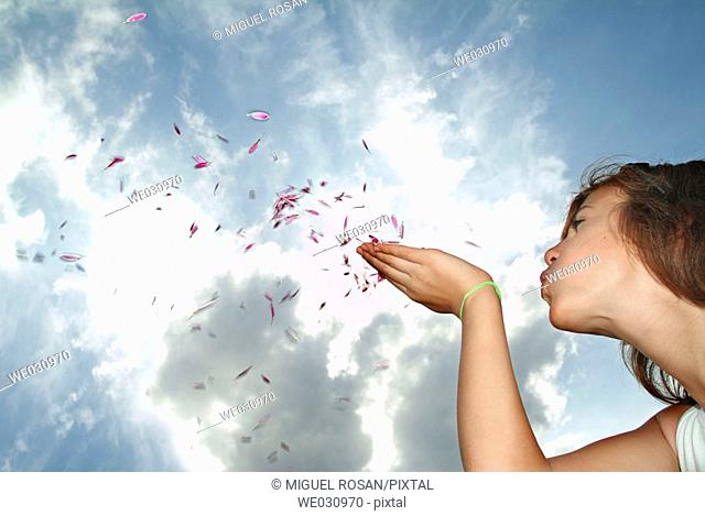 Teenage Girls, blowing into the sky the little petals of a flower