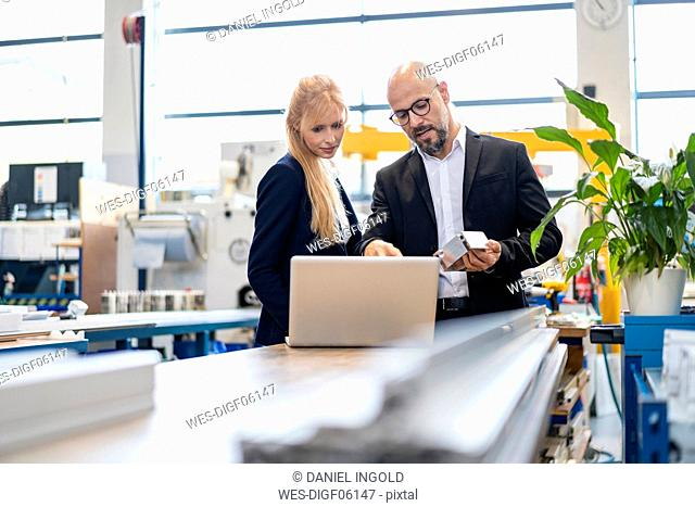 Businessman and businesswoman with laptop and workpiece talking in factory