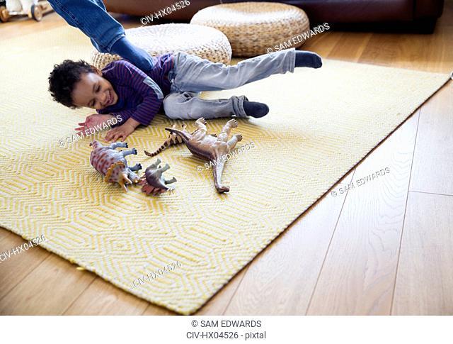 Playful boy with dinosaur toys on living room floor