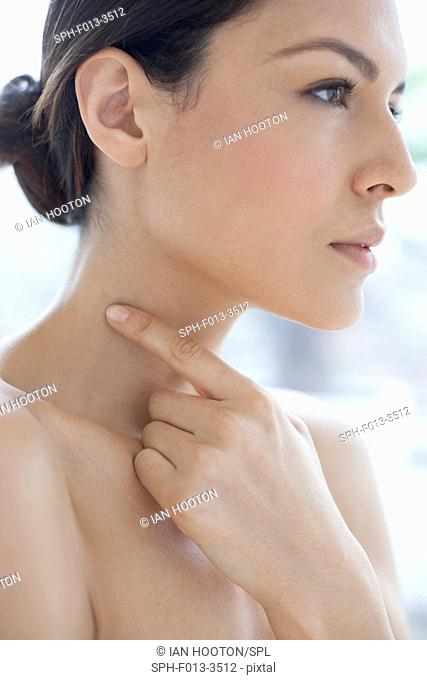 MODEL RELEASED. Young woman pointing to a mole on her neck