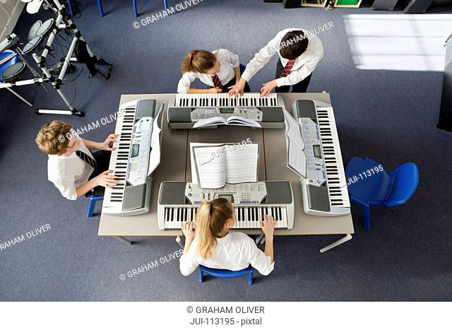 High school students playing pianos in music class