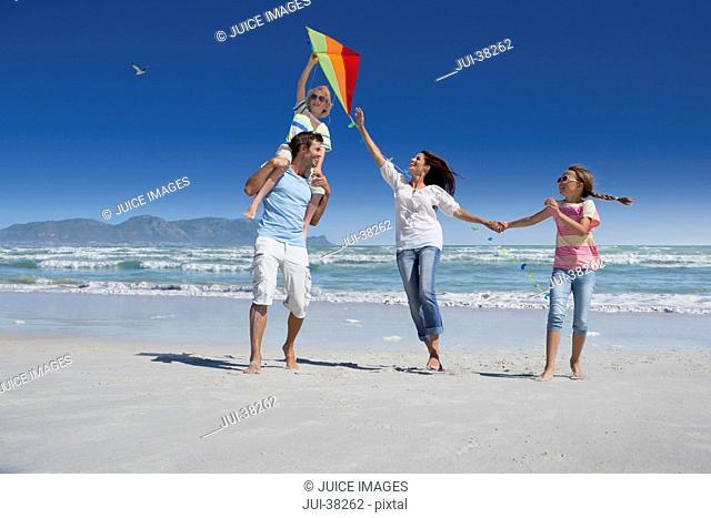 Happy family flying kite on sunny beach