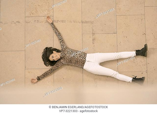 positive minded woman laying on stone floor, stretching arms aside, wearing fashionable leopard print sweater, in Munich, Germany