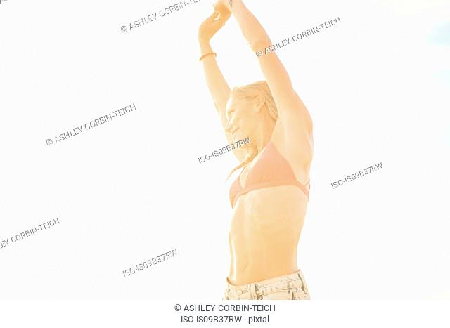 Woman with arms raised looking away