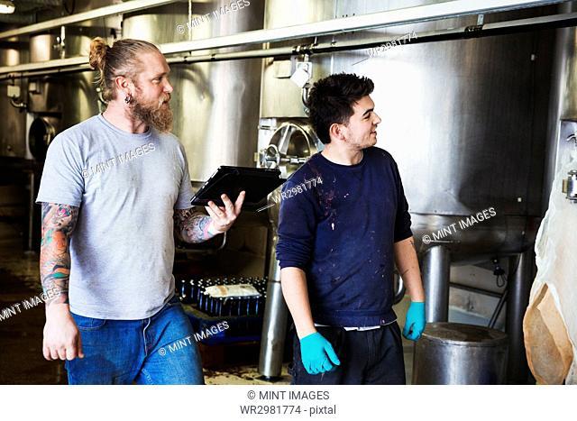 Two men working in a brewery, walking past large metal kettles, holding digital tablet
