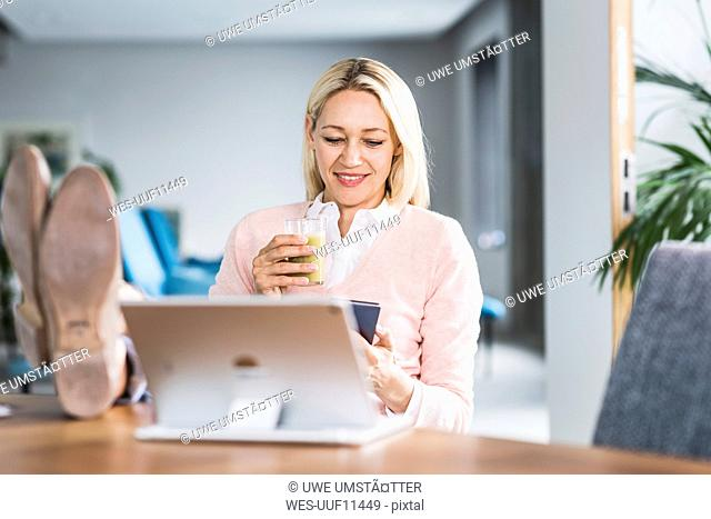 Businesswoman holding smoothie and using cell phone in office
