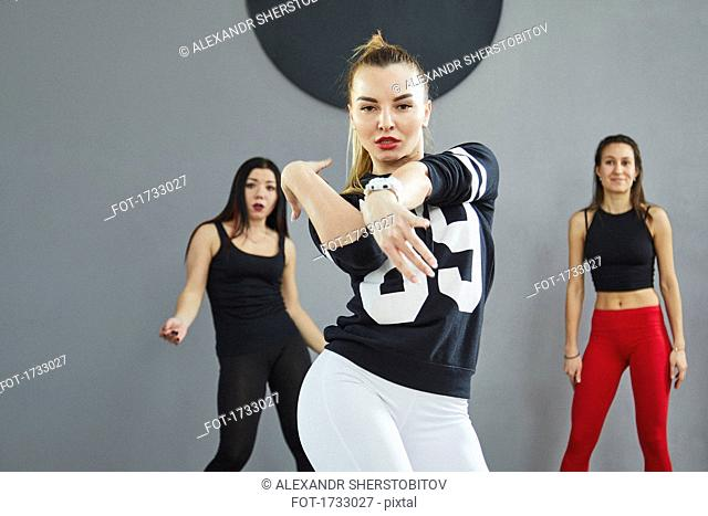Portrait of confident woman dancing with friends standing in background at studio