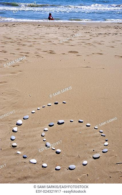 Spiral of pebbles on beach, girl playing in the sea, Provence, France, Europe