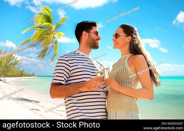 happy couple drinking champagne on tropical beach