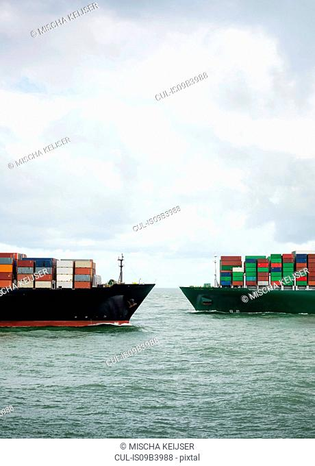 Two large container ships cross each other at entrance of Rotterdam harbour, Netherlands