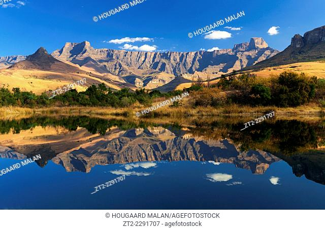 Landscape photo of the amphitheater reflected in a dam surface. Royal Natal National Park, Drakensberg, South Africa