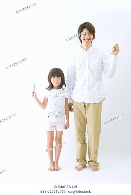 Father and daughter holding toothbrushes