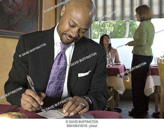 Man signing check in restaurant