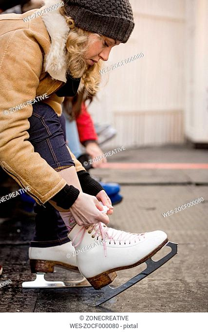 Young woman putting on ice skates