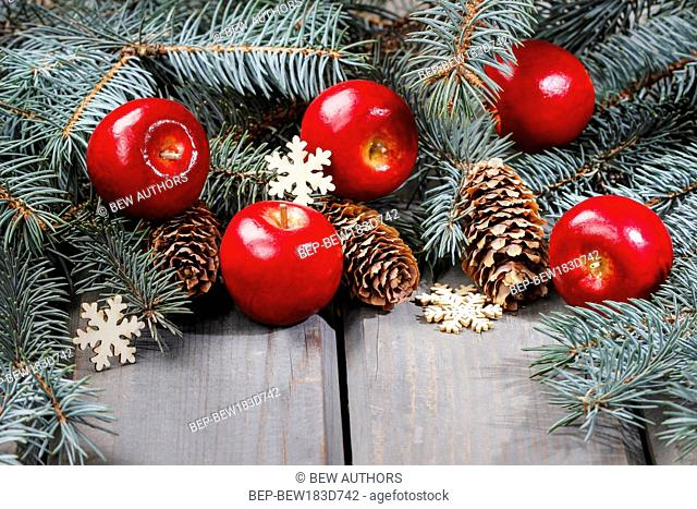 Red apples and fir branch with cones on wooden table. Christmas background, copy space