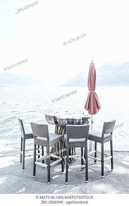 Chairs and a table with parasol on the waterfront on alpine lake Maggiore in Ticino, Switzerland