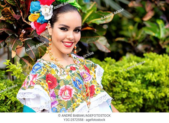 Female teenager, wearing folkloristic Mexican outfit, smiling at camera