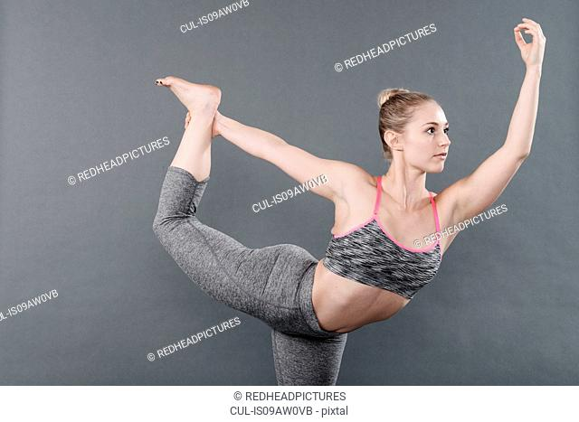 Young woman practising yoga, grey background
