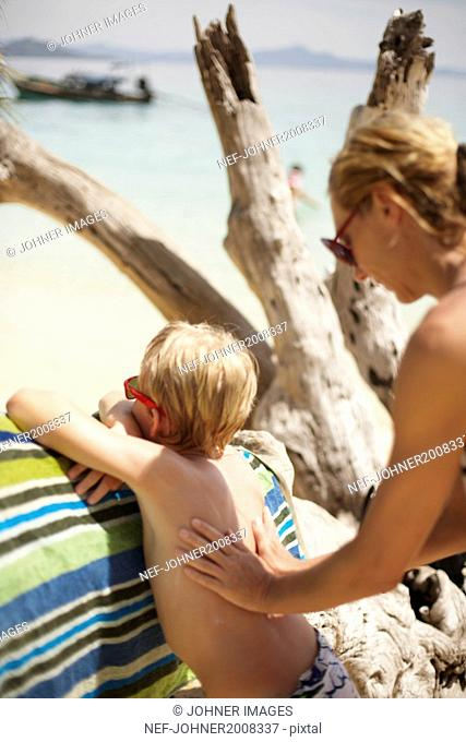Mother applying sun cream on sons back